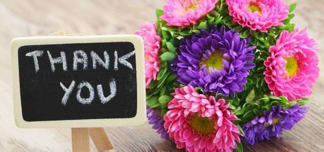 Thank you written on mini blackboard and colorful daisy bouquet
