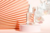 using squalane in skin and hair care, image of squalane in a serum bottle with pink background